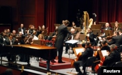 FILE - Syrian-American award-winning classical pianist and composer Malek Jandali, accompanied with an orchestra, plays the piano at the Damascus Opera House, April 1, 2010.