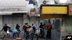 Warga Palestina melemparkan batu-batu dalam bentrokan dengan tentara Israel di kota Hebron, Tepi Barat, setelah Arafat Jaradat, tewas di penjara Israel, Minggu (24/2). (AP/Nasser Shiyoukhi)