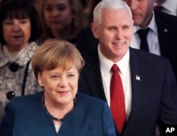 FILE - German Chancellor Angela Merkel and United States Vice President Mike Pence arrive at the Munich Security Conference in Munich, Germany, Feb. 18, 2017.