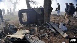 Các giới chức Pakistan xem xét phần còn lại của chiếc xe cảnh sát bị hư hại vì bom vệ đường ở ngoại ô Peshawar, ngày 8/2/2011