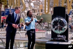 California Governor Gavin Newsom, left, looks on as Access Hollywood personality Scott Evans draws a ball with a winning number during the Vax for the Win lottery contest at Universal Studios in Universal City, Calif., Tuesday, June 15, 2021