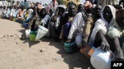 FILE - Internally displaced persons wait to be served with food at Dikwa camp, in northeast Nigeria's Borno state, Feb. 2, 2016.