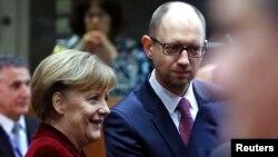 Kanselir Jerman Angela Merkel (kiri) berbicara dengan PM Ukraina Arseniy Yatsenyuk dalam pertemuan pemimpin Uni Eropa di Brussels, Belgia (foto: dok).
