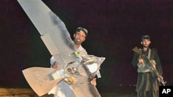 Một người dân làng Pakistan cầm mảnh vỡ mà người ta nghi là của một chiêc máy bay trinh sát không người lái bị rơi ở thị trấn Chaman trong vùng biên giới Pakistn giáp ranh với Afghanistan