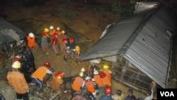 ພວກດັບເພີງຊ່ວຍກັນກູ້ເອົາປະຊາຊົນ ອອກມາຈາກເຮືອນຫລັງນຶ່ງ ທີ່ຖືກດິນເຈື່ອນທັບ ໃນເມືອງ Chittagong, ປະເທດ Bangladesh, ວັນທີ 26 ມິຖຸນາ 2012.
