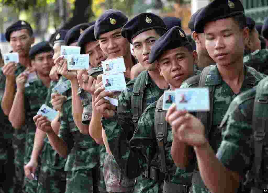 Thai soldiers pose with their identity cards as they wait in a line to vote at a polling station in Bangkok, Feb. 2, 2014.