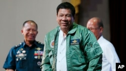"Philippine President Rodrigo Duterte, center, smiles as he is presented with a pilot's jacket during his ""Talk with the Airmen"" on the anniversary of the 250th Presidential Airlift Wing Tuesday, Sept. 13, 2016 at the Philippine Air Force headquarters in suburban Pasay city, southeast of Manila, Philippines. On Monday, President Duterte, in his first public statement opposing the presence of American troops, said he wants U.S. forces out of his country's south and blamed the United States for inflaming Muslim insurgencies in the region."