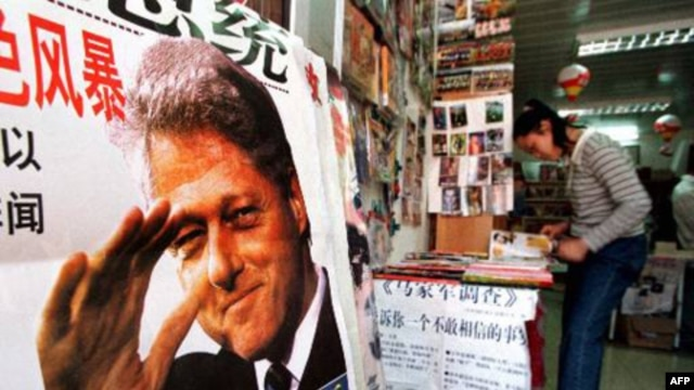 """A poster advertises a book about President Clinton at a Beijing bookstore in May 1998, shortly before he visited China. The poster declares his troubles as the """"number one sex scandal in the world."""""""
