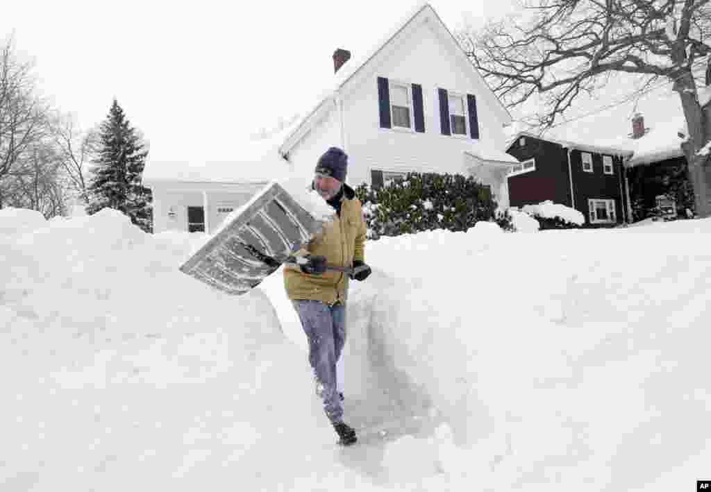 Tom Mulkern, de Norwood, Mass., enlève de la neige avec une pelle devant sa maison le dimanche 15 février 2015, à Norwood.