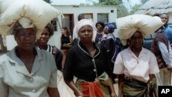 FILE: Unidentified rural women in Seke, Zimbabwe, 120 kilometres east of Harare, carry bags of donated maize from a food distribution point on Monday, Oct. 7, 2002. Seke is just one of many food distribution centers throughout Zimbabwe, which have been se