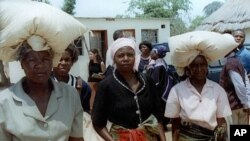 FILE: Unidentified rural women in Seke, Zimbabwe, 120 kilometres east of Harare, carry bags of donated maize from a food distribution point. (AP)