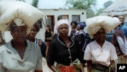 FILE: Unidentified rural women in Seke, Zimbabwe, 120 kilometres east of Harare, carry bags of donated maize from a food distribution point.