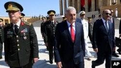 Turkish Prime Minister Binali Yildirim, center, walks with chief of general staff General Hulusi Akar at the Mausuleum of modern Turkey's founder, Mustafa Ataturk, in Ankara, July 28, 2016.