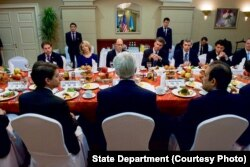 Kerry, back to camera, has a breakfast meeting with members of the American Chamber of Commerce in Kazakhstan, in Astana. Executive director Doris Bradbury is among the diners facing him.