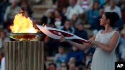 Aktris Ino Menegaki, berperan sebagai pendeta, menyalakan obor dengan api Olimpiade di dalam upacara serah terima di Stadion Panathinaiko (5/10).