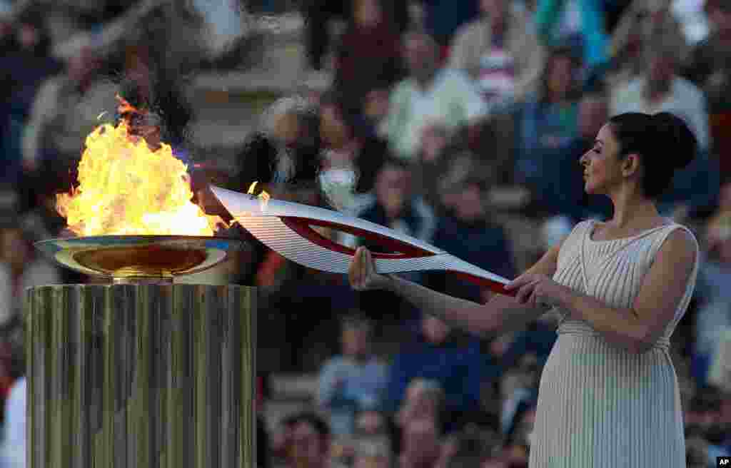 Actress Ino Menegaki, playing the role of high priestess, lights the torch with the Olympic Flame during a handover ceremony in Athens' Panathinaiko Stadium, Greece. After a seven-day run through Greece, the flame will cover 40,000 miles on Russian soil.