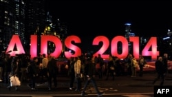 People gather next to a sign reading AIDS 2014 in Melbourne on July 18, 2014 after news that downed Malaysia Airlines flight MH17 was carrying many participants headed to the 20th International AIDS Conference planned this weekend in the Australian city.