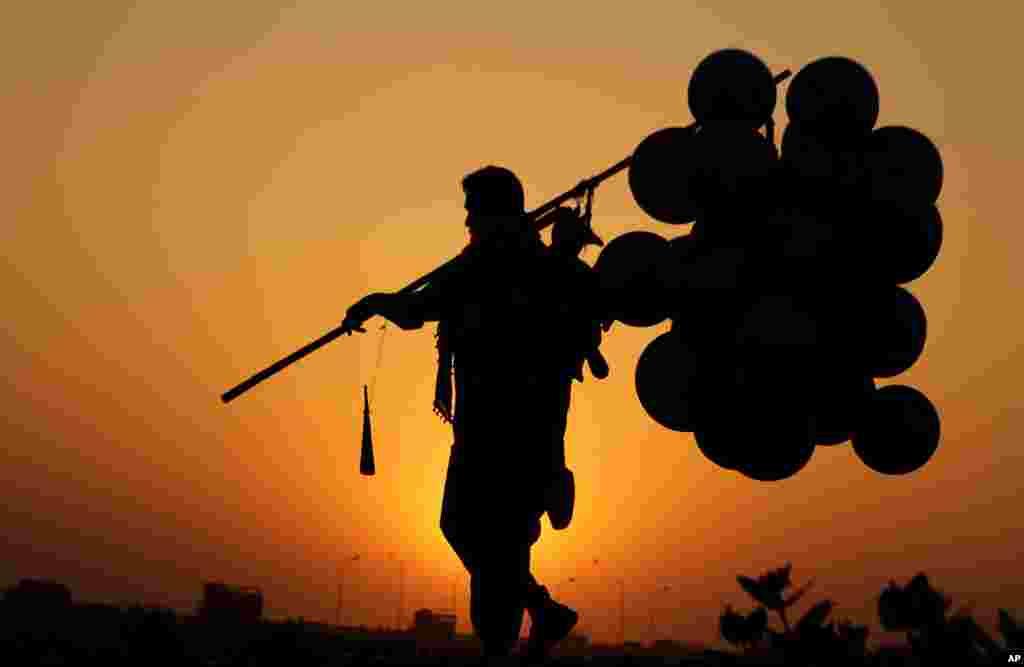 Seorang penjaja balon membawa pulang barang dagangannya yang tersisa, saat matahari terbenam di kota Lahore, Pakistan.