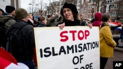 FILE - A woman holds a placard at a rally calling against immigration and what demonstrators see as the Islamization of their communities, in Amsterdam, Netherlands, Feb. 6, 2016.