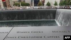 Nhiều người đến tưởng nhớ thân nhân đã khuất đặt tay lên trên nền đá hoa cương khắc tên các nạn nhân