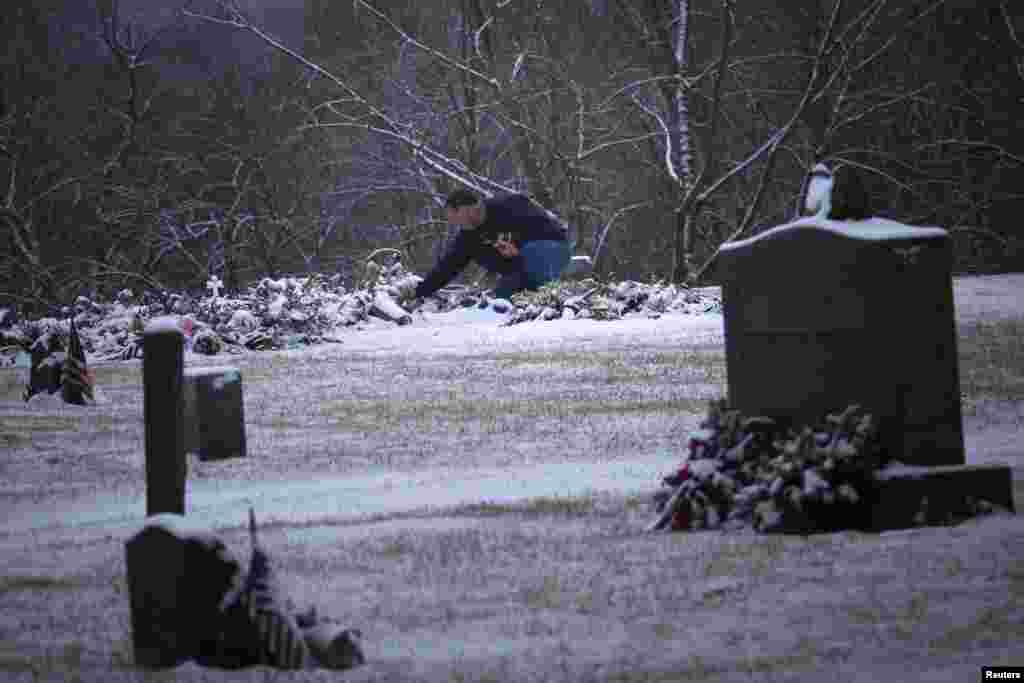 A man touches the snow covered grave of six-year-old Ana Grace Marquez-Greene, one of 20 schoolchildren killed in the December 14 shootings at Sandy Hook Elementary School, at the Newtown Village Cemetery, Connecticut, December 25, 2012.