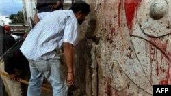 Nhân viên an ninh Pakistan kiểm tra hiện trường sau vụ nổ bom ở Karachi, ngày 30/8/2011
