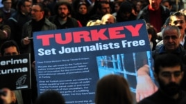 Turkish journalists carry a large sign displaying a letter to Turkish Prime Minister Recep Tayyip Erdogan that calls for the release of jailed journalists, during a demonstration on Istiklal Avenue in Istanbul, on March 13, 2011.