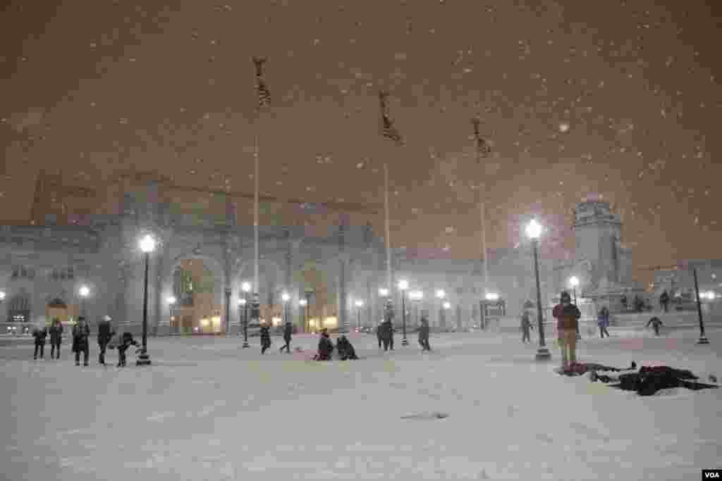 Walaupun salju tebal turun, orang-orang berkumpul untuk membuat boneka salju di depan Union Station, Washington. (P. Datcher/VOA)