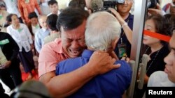 Soum Rithy (C), who lost his father and three siblings during the Khmer Rouge regime, breaks out in tears and hugs another survivor after the verdict was delivered in the trial of former Khmer Rouge head of state Khieu Samphan and former Khmer Rouge leade
