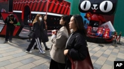 Shoppers walk by a promotion by Alibaba's Tmall online shopping platform for the upcoming 10th Singles Day event in Beijing, China, Nov. 7, 2018. The holiday began in the '90s by Chinese college students as a version of Valentine's Day for people without romantic partners.