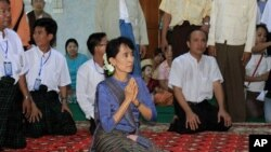 Burmese democracy icon Aung San Suu Kyi, center, pays her respects to a senior Buddhist monk during her visit to a Buddhist monastery in Bago, north of Yangon, Burma, August 14, 2011