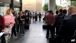 FILE - Immigrants awaiting deportation hearings line up outside the building that houses the immigration courts in Los Angeles, June 19, 2018. (AP Photo/Amy Taxin, File)