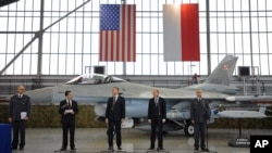 波兰军队军备总督查斯泽帕尼亚克将军、美国驻波兰大使斯蒂芬·马尔、波兰副总理兼国防部长谢莫尼亚克和其他官员在波兰波兹南的一处空军基地签署协议。(2014年12月11日 资料照片)
