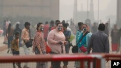 Indian and foreign tourists wear pollution mask and take a walk at the India Gate amidst morning smog in New Delhi, India, Monday, Nov. 4, 2019. (AP Photo/Manish Swarup)
