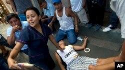 Ông Ruben Mero được nhân viên y tế săn sóc sau khi ngất xỉu vì quá đau buồn trong đám tang của cháu gái tại Montecristi, Ecuador, ngày 19/4/2016.