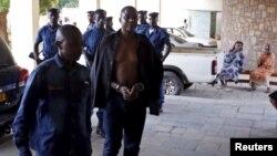 Polisi mengawal jenderal angkatan darat Burundi yang ditahan, Juvenal Niyungeko, ke pengadilan tinggi di Bujumbura, Burundi (16/5). (Reuters/Goran Tomasevic)