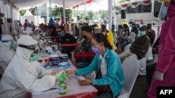 Warga ikut berpartisipasi dalam test cepat gratis Covid-19 di Surabaya, 2 Juni 2020. (Foto: Juni Kriswanto / AFP)