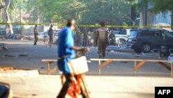Un passant à vélo regarde le personnel militaire à l'extérieur du quartier général des forces de défense du pays après la double attaque contre l'ambassade de France et l'armée du pays, à Ouagadougou le 3 mars 2018.