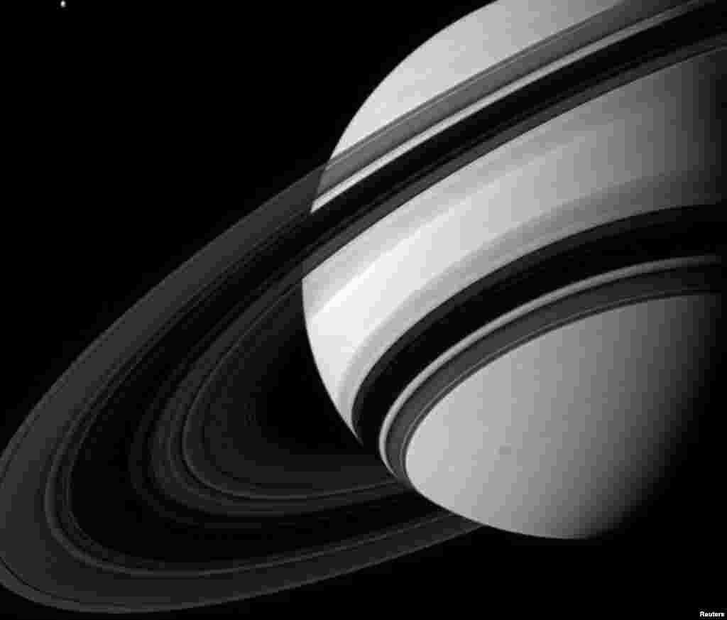 ماه تتيس (سمت چپ – بالای تصوير) در کنار سياره زحل در اين عکس از فضاپیمای کاسینی ناسا در ۱۹ اوت ۲۰۱۲ مشاهده می شود. حلقه های زحل ماه تتيس با عرض ۱۰۶۲ کيلومتر را بسيار کوچک جلوه می دهد؛ هر چند دانشمندان معتقدند که حجم ماه از کل سيستم حلقه های زحل بزرگتر است. اين عکس از فاصله ۲ ميليون و ۴۰۰ هزار کيلومتری زحل گرفته شده است. (رويترز / ناسا)