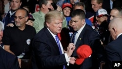 Republican presidential candidate Donald Trump signs a hat after a rally in Novi, Mich., Sept. 30, 2016.