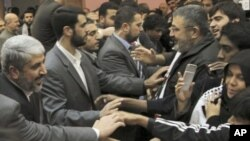 Hamas leader Khaled Meshaal (l) greets members of the 'Asia 1' convoy after a meeting in Damascus, 22 Dec 2010