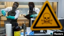 FILE - Employees of an OPCW-linked lab inspect dummy samples contaminated with a substance similar to Sarin during a demonstration in Muenster, Germany, Oct. 15, 2013.