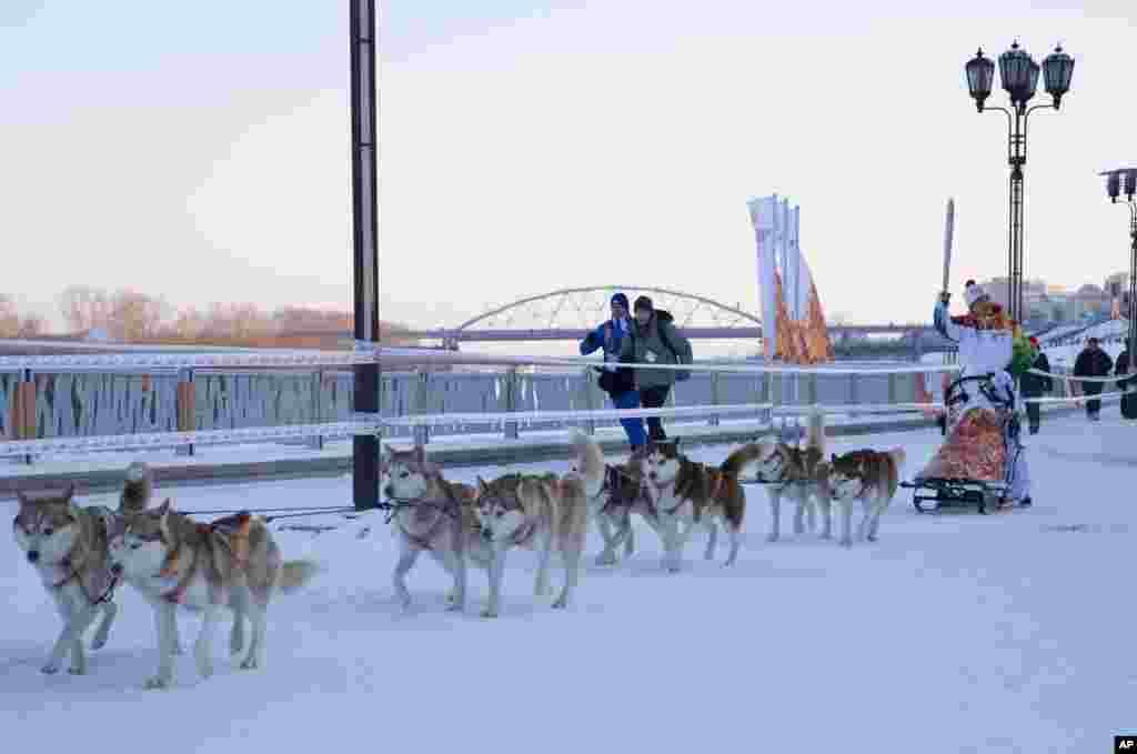 Pembawa obor olimpiade musim dingin Sochi, Mikhail Fateyev, membawa obor dengan naik kereta anjing di atas lapisan salju di pinggir sungai Tura, Tyumen, Siberia barat, Rusia.