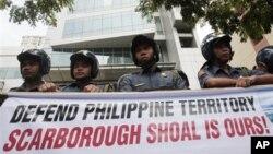 Cảnh sát Philippines đứng sau biểu ngữ của người biểu tình bên ngoài lãnh sự quán Trung Quốc ở khu tài chính của Makati.