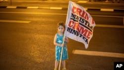 一個女孩9月6日星期天在總理官邸外的廣場的抗議活動中舉旗。