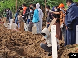 Relatives attend funerals of family members who died from the coronavirus at a cemetery for COVID-19 victims in TPU Rorotan, north Jakarta, Indonesia, July 8, 2021. (Indra Yoga/VOA Indonesian)