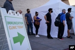 FILE- People wait in line for COVID-19 vaccinations at an event at La Bonita market, a Hispanic grocery store, in Las Vegas, July 7, 2021.