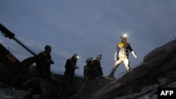 FILE - Members of the Syrian Civil Defence, also known as the White Helmets, search for survivors following an airstrike on the flashpoint town of Maaret al-Numan in Syria's northwestern Idlib governorate, Dec. 30, 2019.