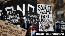 "People with banners and posters attend a demonstration against the ""Global Security Bill' that rights groups say would make it a crime to circulate an image of a police officer's face and would infringe journalists' freedom in France."
