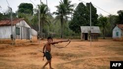 A member of Uru Eu Wau Wau tribe holds up a rifle in the tribe's reserve in the Amazon, south of Porto Velho, Brazil, Aug. 29, 2019.